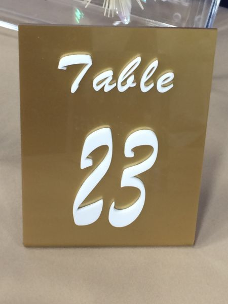 Gold table sign with raised numbers: Swipe To View More Images